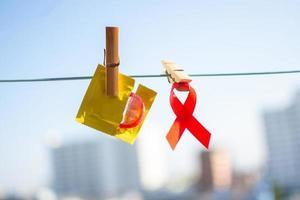 rotes Band und Kondom auf Wäscheklammer foto
