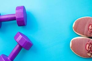 Hanteln und Laufschuhe auf blauem Hintergrund foto