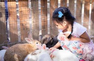 junges asiatisches Mädchen, das mit Farmkaninchen sozialisiert foto