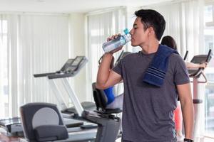 Mann Trinkwasser in der Turnhalle foto
