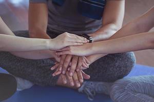 drei Erwachsene mit den Händen zusammen im Fitnessstudio.