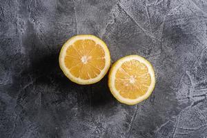 eine in zwei Hälften geschnittene Zitrone auf grauem Betonhintergrund foto