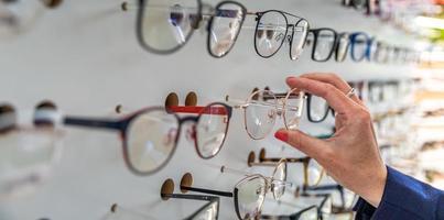 Frau wählt Brille in einem Einzelhandelsgeschäft foto