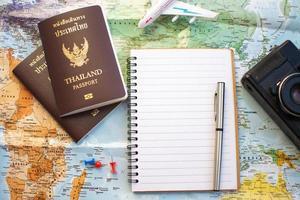 Notizbuch mit Reisepass neben Karte foto