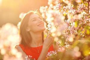 junge Frau im roten Kleid, das im Garten geht foto