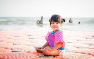 kleines asiatisches Mädchen, das am Strand lächelt