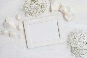 weißer Holzrahmen mit Herzen und Blumen foto