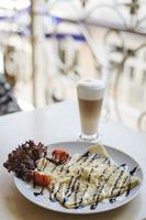 Crêpe-Frühstück mit Latte auf dem Balkon