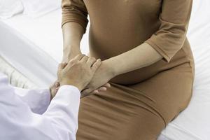 Geburtshelfer hält Hände der schwangeren Patientin foto