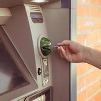 Der Kunde verwendet Geldautomaten, um Bargeld abzuheben foto