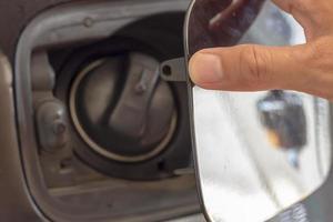 Nahaufnahme einer Hand, die die Kraftstofftankklappe am Auto öffnet foto