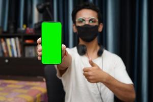 junger indischer Junge, der ein Telefon mit grünem Bildschirm hält foto