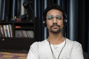 junger indischer Junge, der Kopfhörer trägt