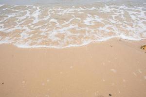 Strandsand und Welle foto