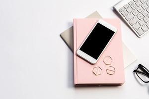 flache Lage von rosa Notizbuch und Büroartikeln foto