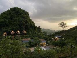 Hütten zwischen Bäumen und Bergen foto