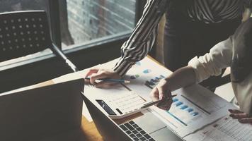 Zwei Geschäftsfrauen analysieren Diagramme und arbeiten am Laptop foto