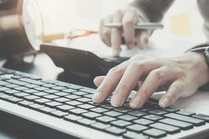 Business-Profi tippt auf der Tastatur, während Sie den Taschenrechner verwenden foto
