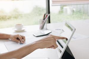 Geschäftsfrau zeigt auf Tablet-Bildschirm foto