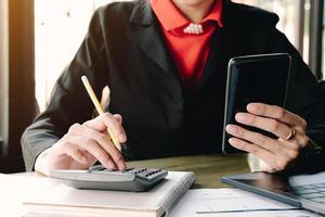 Geschäftsfrau, die Smartphone betrachtet und Taschenrechner verwendet foto