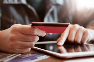 Person, die Kreditkarte während der Verwendung des Tablets hält foto