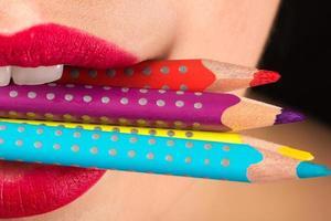 Frau beißt Buntstifte