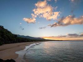 Meereswellen, die während des Sonnenuntergangs am Ufer abstürzen foto