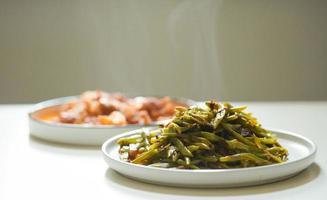 grüne Bohnen und Eintopf auf weißen Tellern