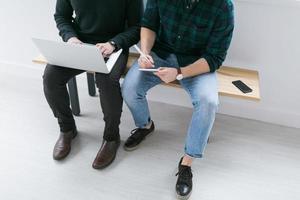 zwei junge Männer, die zusammen an einem Projekt arbeiten foto