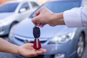ein Autoverkäufer, der einem neuen Fahrzeughalter einen Schlüssel übergibt foto