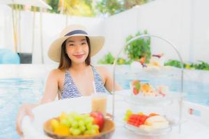 Frau, die Nachmittagstee durch Schwimmbad genießt foto