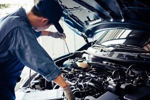 Der Automechaniker führt eine Inspektion am Fahrzeug durch foto