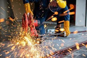 Funken fliegen, während ein Schweißer auf der Baustelle Stahl schneidet foto