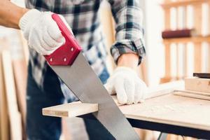 Nahaufnahmeporträt des Handwerkers, der Holz in der Werkstatt schneidet foto