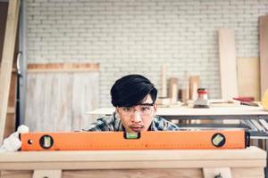 Flachwinkelansicht des Tischlers, der in der Werkstatt arbeitet foto