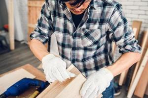 Handwerker klebt Holz in der Werkstatt zusammen foto