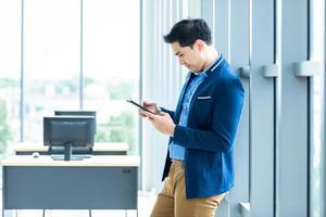 junger asiatischer Unternehmer mit mobilem Tablet bei der Arbeit
