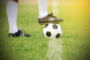 Fußballspieler, der mit Ball auf dem Feld steht foto