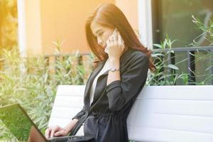 junge professionelle asiatische Frau benutzt ihren Laptop und Telefon auf einer Bank foto