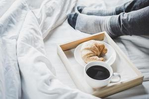 junge Frau auf dem Bett mit dem Frühstück genießen foto