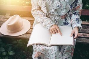 Frau zeigt auf leeres Buch im Park foto