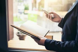 junge attraktive Geschäftsfrau, die nahe Fenster steht und am Smartphone mit Berichtsbuch arbeitet, führendes Mädchen, das online lernt foto