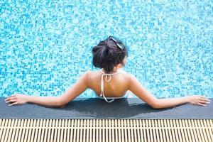 Frau, die sich im Schwimmbad entspannt foto