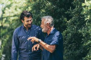 alter Vater und erwachsener Sohn entspannen sich im Hinterhof