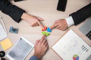 Gruppe von Geschäftsleuten zeigen auf Kreisdiagramm