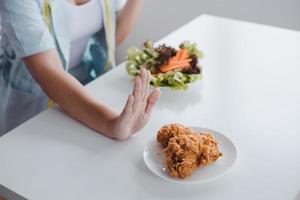 Frau auf Diät lehnt ungesundes Essen am Tisch ab
