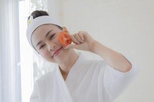 Frau hält Tomatenscheibe ins Gesicht