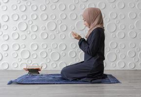 muslimische Frau kniet im Gebet foto