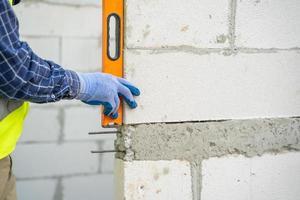 Nahaufnahme eines Bauarbeiters mit Ebene in der Hand foto