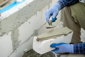 Bauarbeiter, der Gips auf einen Ziegelstein aufträgt foto
